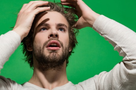morning wake up of man with beard and long hair in white underwear on green background, barbershop Stock Photo