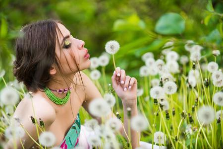 Jonge vrouw met modieuze make-up en kralen in groene bladeren en paardebloem bloem op natuurlijke achtergrond, schoonheid en mode, jeugd en frisheid