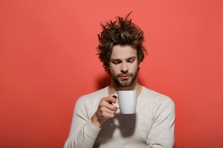 uncombed: man with morning tea cup has uncombed hair