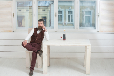 Hipster with beard and moustache sitting on wooden chair at table with bottle and glass of red wine. Brutal man indoors on white window background. Alcohol and convive. Unhealthy lifestyle. Bad habits 版權商用圖片