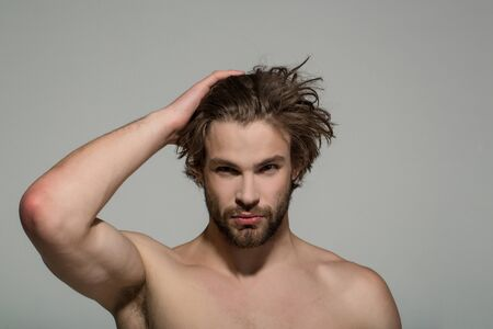 handsome man with beard and stylish hair with raised hand and bare chest on grey background, morning and fashion