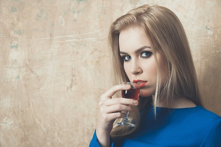 Woman drinking red liqueur in glass. Girl with blond long hair, make up in blue dress on beige wall. Alcohol, appetizer, bad habits, addictive and convive. Unhealthy lifestyle, copy space 版權商用圖片