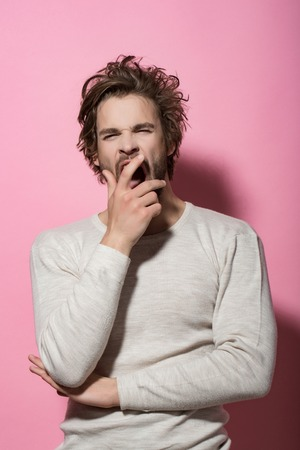 sleepy man with disheveled and uncombed long hair with beard on yawning face in white underwear on pink background, morning and wake up, everyday life, barbershop