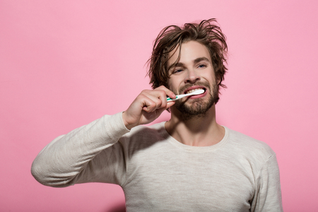 morning dental care of man brush teeth with toothpaste on pink background Stock Photo