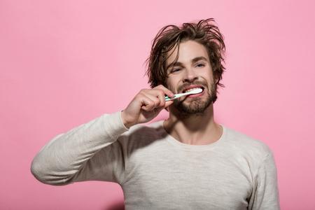 ochtend tandheelkundige zorg voor man tanden poetsen met tandpasta op roze achtergrond