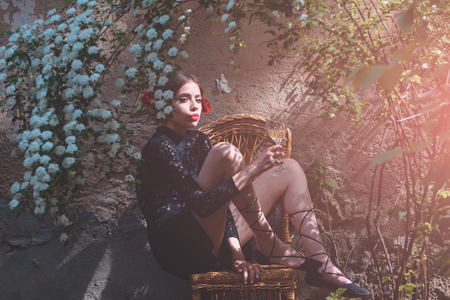girl or pretty woman, fashion model with red lips, makeup and wine glass sitting on wicker chair in yard on outdoor wall. Alcohol drinking. Enjoying life. Holiday celebration. Spring, summer