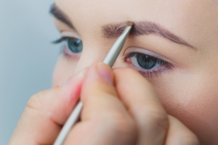 Woman with blue eyes getting makeup on brows with brush. Male hand applying brown color on girl eyebrow with young healthy face skin on grey background. Visage, cosmetics and make up. Beauty salon
