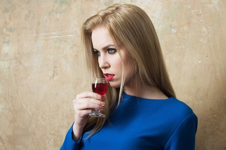 Woman in blue dress drinking red liqueur in glass. Girl with blond long hair and make up on beige wall. Alcohol, appetizer, bad habits, addictive and convive. Unhealthy lifestyle, copy space