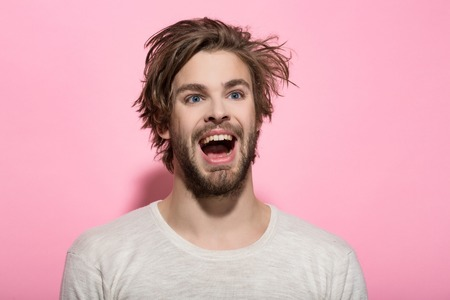 happy man with long stylish uncombed hair and smiling bearded man on pink background, morning and barbershop fashion