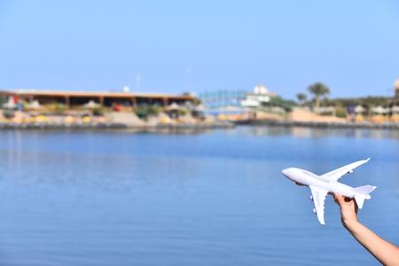 Vrouwelijke hand met wit model van vliegtuigvervoer op achtergrond van aard met blauwe hemel en water, die over avonturen, exemplaarruimte dromen