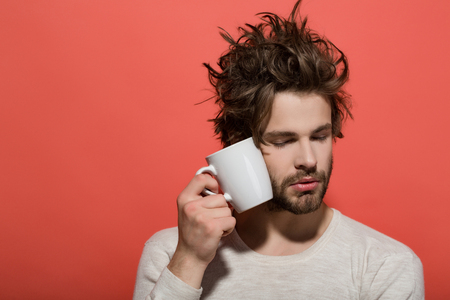 sleepy man with cup of tea or coffee has uncombed hair in underwear on red background, morning refreshment and drink, copy space
