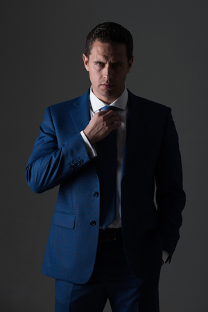 Successful man, confident businessman or handsome boss adjusting tie in stylish blue formal suit and white shirt on grey background. Business, fashion and success. Dress code and accessories Фото со стока