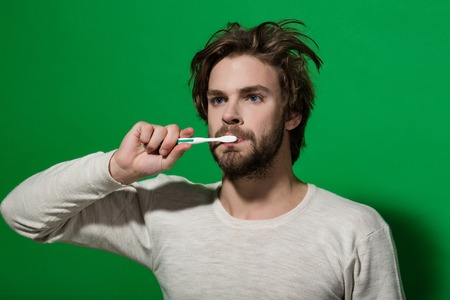 hygienic: dental health of metrosexual man brush teeth with toothpaste on green background, morning hygiene and spa