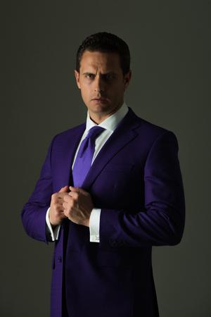 男。自信を持っているビジネスマンやファッショナブルなフォーマル スーツとグレーの背景に白シャツでネクタイを調整成功した上司。ビジネス、