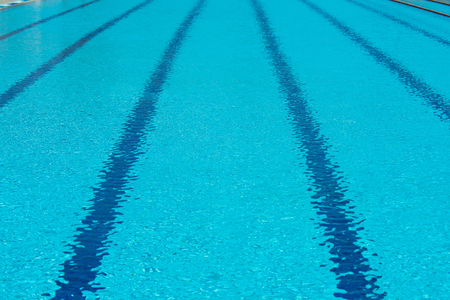 Empty swimming pool with blue clear trasparent water and rope lines backgound, sport training concept Фото со стока