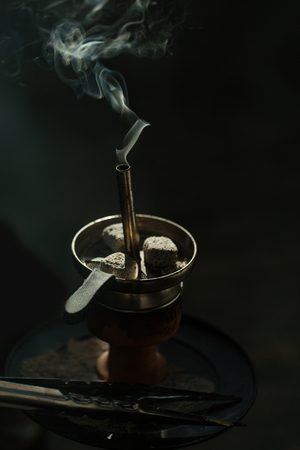 Carbón de carbón de leña en una taza metálica con humo y pinzas o herramienta de afeitar en el fondo negro . el consumo de drogas y narcóticos y énfasis Foto de archivo - 82059513