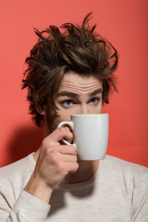 surprised man with cup of tea or coffee has uncombed hair in underwear on red background, morning refreshment and drink, energy