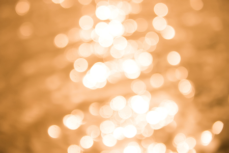 Sparkling shining bokeh yellow golden abstract background beautiful glossy sunlights on water Stock Photo