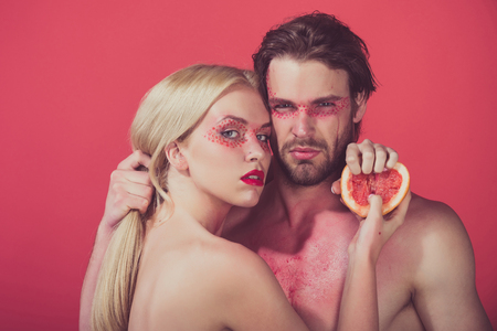 vitamine: young couple of woman and man with creative fashionable makeup on face hold grapefruit fruit on red background, beauty and fashion, allergy, healthcare and vitamin, vegetarian and dieting