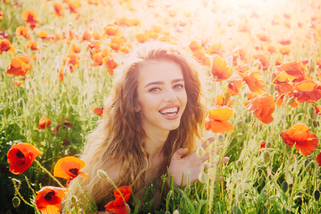 woman or happy smiling girl with long curly hair hold flower in field of red poppy seed with green stem on natural background, summer, spring, drug and love intoxication, opium