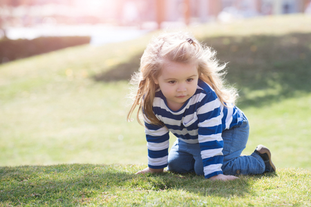 Boy little child with adorable thoughtful face with long blond hair in blue and white striped shirt and jeans crawling on his knee on meadow with green grass in summer day