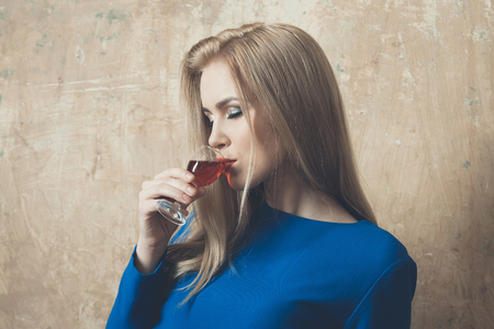 Girl enjoying red liqueur in glass. Woman with blond long hair, make up in blue dress on beige wall. Alcohol, appetizer, bad habits, addictive and convive. Unhealthy lifestyle, copy space