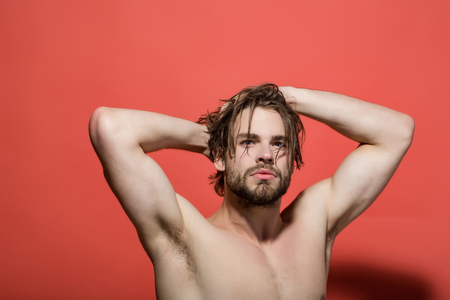 morning wake up of man with beard and long hair has bare chest on red background with raised hands and biceps, barbershop