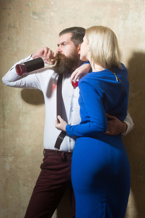 Man drinking wine from bottle and hugging girl with glass of liqueur. Sexy woman in blue dress and brutal hipster on beige wall. Couple in love. Alcohol and convive. Unhealthy lifestyle. Bad habits Stock Photo