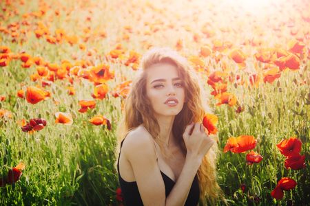 poppy seed and girl with long curly hair in red flower field with green stem on natural background, summer, spring, drug and love intoxication, opium