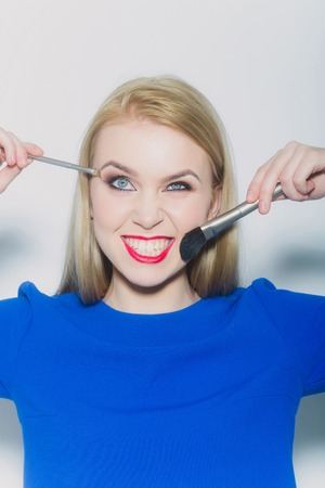 Girl winking and smiling with makeup brushes. Funny woman with long blond hair in blue dress on white. Grimace and facial expression. Strabismus. Visage and make up