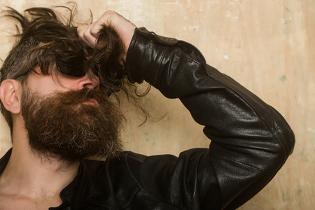 man with long hipster beard and mustache in glasses and leather jacket with raised hand on textured wall background