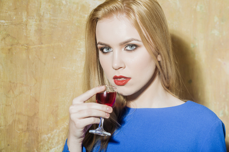 Girl drinking glass of red liqueur. Woman with blond long hair, make up in blue dress on beige wall. Alcohol, appetizer, bad habits, addictive and convive. Unhealthy lifestyle, copy space