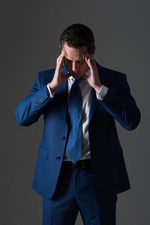 ボス、ハンサムな男やスタイリッシュな髪の実業家感じ頭痛、ファッショナブルなフォーマル スーツ、白いシャツ、グレーの背景にネクタイで散髪