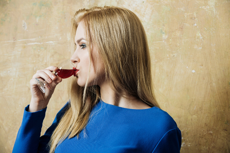 Woman drinking red wine in glass. Girl with blond long hair, make up in blue dress on beige wall. Alcohol, appetizer, bad habits, addictive and convive. Unhealthy lifestyle, copy space