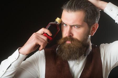 Homme tenant une bouteille de liqueur rouge au visage froncer les sourcils. Hipster avec barbe, moustache et coupe de cheveux isolé sur noir. Alcool, apéritif et apéritif. Addictif et convive. Mode de vie malsain. Mauvaises habitudes