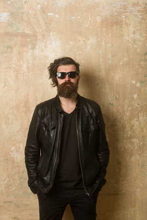 Man with long beard and mustache. Hipster in leather jacket and glasses. Guy with serious face. Fashion model on textured wall background. Biker fashion and beauty. Imagens