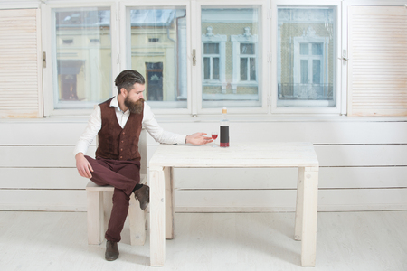 Man with glass and bottle of wine on table sitting on wooden chair. Caucasian hipster with beard and moustache in room with white window. Alcohol and convive. Unhealthy lifestyle. Bad habits