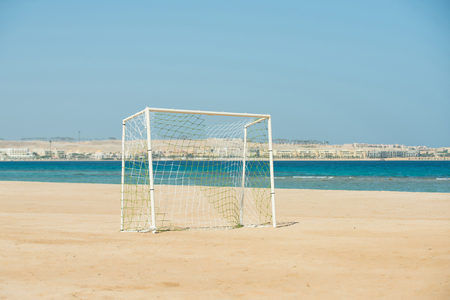 Soccer goal post with white net standing on coastline with beautiful blue sky and sea landscape on natural summer background
