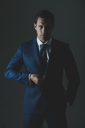 代表取締役社長。真面目な顔とスタイリッシュな髪、灰色の背景にファッショナブルなブルーのフォーマルなスーツでポーズをとって散髪ビジネス 写真素材