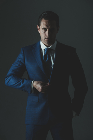 ceo. businessman or man manager with serious face and stylish hair, haircut posing in fashionable blue formal suit on grey background. Business, fashion and success