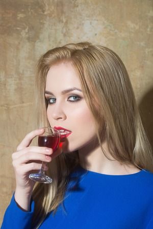 Woman drinking glass of red liqueur. Girl with blond long hair, make up in blue dress on beige wall. Alcohol, appetizer, bad habits, addictive and convive. Unhealthy lifestyle 版權商用圖片