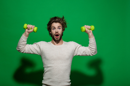 surprised man with barbell or dumbbell workout, has disheveled and uncombed long hair and beard on face in white underwear on blue background, morning exercise and wake up, barbershop, sport Imagens