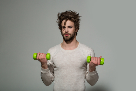 man with barbell or dumbbell workout, has disheveled and uncombed long hair and beard on face in white underwear on grey background, morning exercise and wake up, barbershop, sport Stock Photo