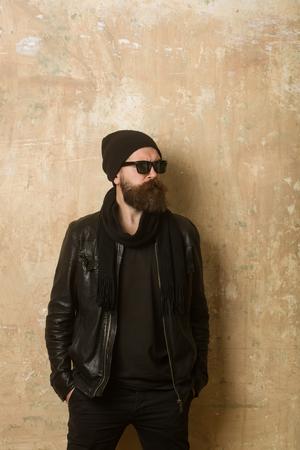 革のジャケットとメガネと帽子で流行に敏感。テクスチャ壁背景ファッション モデル。深刻な顔を持つ男。バイカー ファッションと美容。長いひげ 写真素材