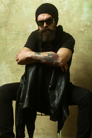 Biker fashion and beauty. Fashion model on textured wall background. Hipster in leather jacket and hat with glasses. Man with long beard and mustache. Guy with serious face. Reklamní fotografie