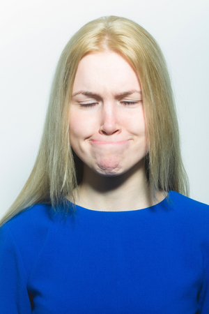 Woman with closed eyes hiding lips in mouth isolated on white. Girl with young healthy skin and no makeup. Fashionable model with long blond hair in blue dress. Grimace and facial expression Stock Photo