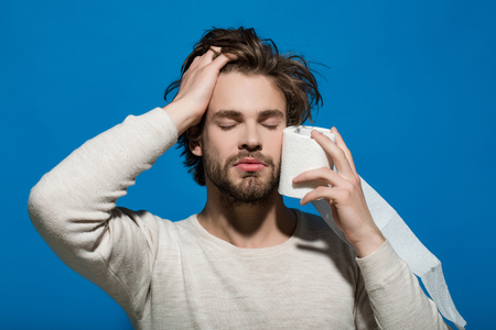 man with closed eyes and sleepy face hold toilet paper in underwear on blue background