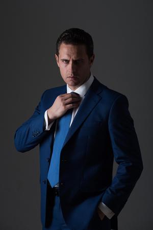 男は、自信を持っているビジネスマンやファッショナブルなフォーマル スーツとグレーの背景に白シャツでネクタイを調整成功した上司。ビジネス
