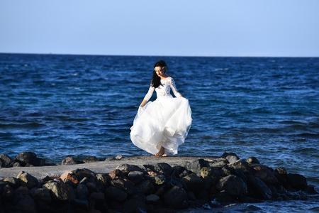 花嫁屋外ビーチと青い海を歩いているエレガントな白いドレスで単独で美しい女性 写真素材