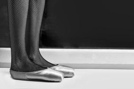 benen of voeten van danser of ballerina in balletschoenen en netkousen staan op de vloer, kopie ruimte, zwart en wit